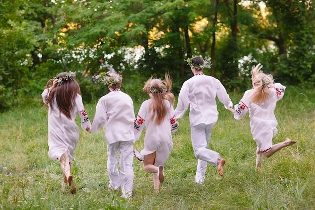 В середине лета. люди бегают на природе в славянской одежде.