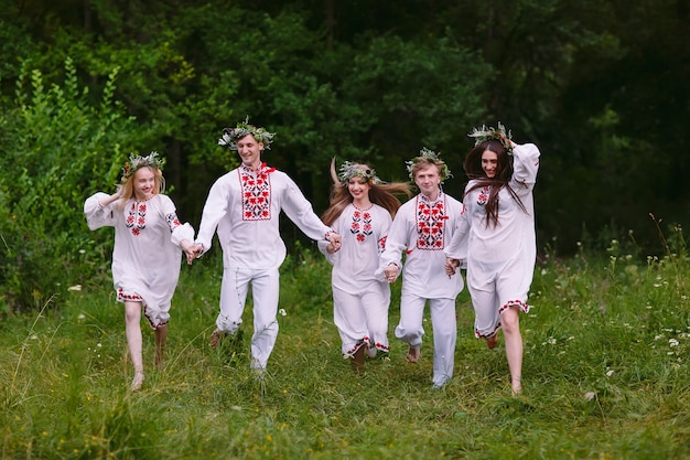 Midsummer, people running in nature in slavic clothes.