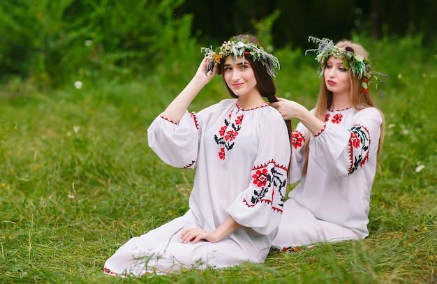 真夏。スラブの服を着た2人の女の子が、火のそばの髪に三つ編みを織ります。