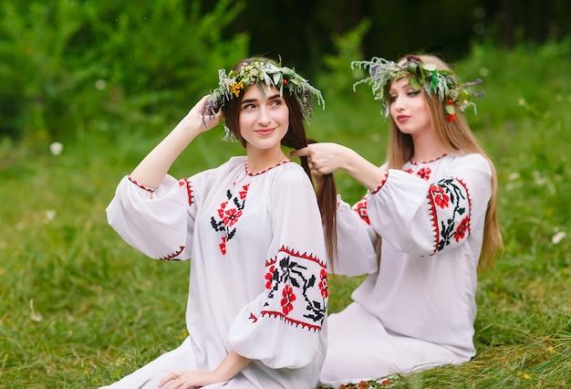 В середине лета. две девушки в славянских одеждах плетут косы в волосы у костра.