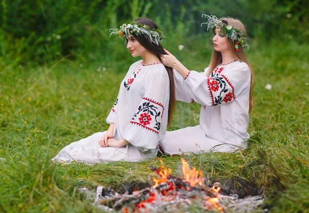 Середина лета. две девушки в славянских одеждах плетут косы в волосы у костра.