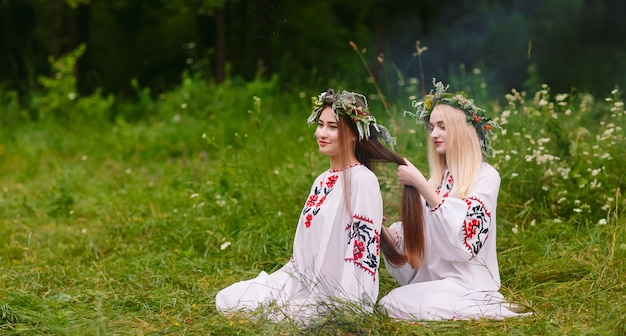 Midsummer. two girls in the slavic clothes weave braids in the hair near the fire.