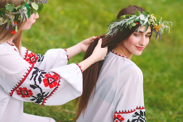 Midsummer. two girls in the slavic clothes weave braids in the hair