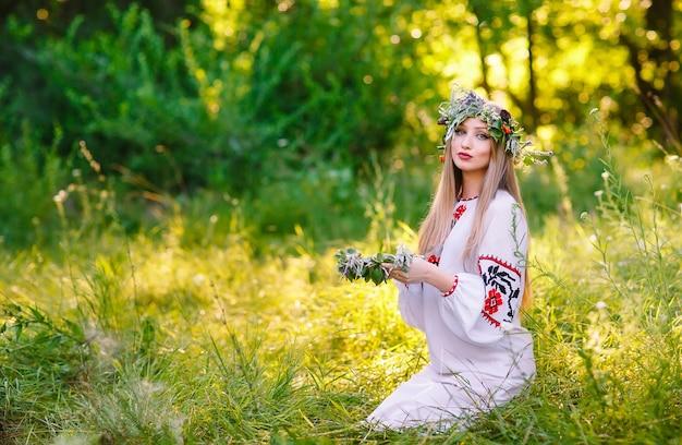 В середине лета. женщина плетет венок у костра.
