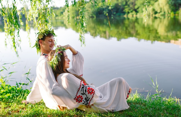 Середина лета. молодые влюбленные в славянских костюмах на берегу озера. славянский праздник ивана купалы.
