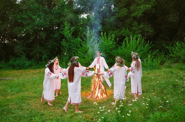 В середине лета. молодые люди в славянской одежде танцуют в лесу у костра.