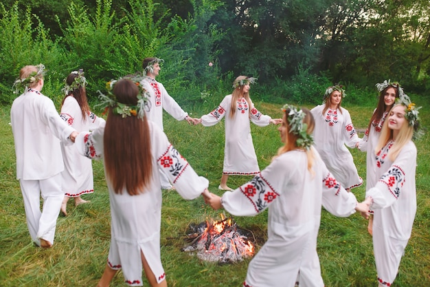 В середине лета. молодые люди в славянской одежде вращаются вокруг пожара в середине лета. ,