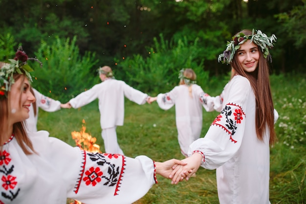 В середине лета. молодежь в славянской одежде кружится вокруг костра в летнее время. .