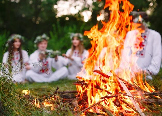Лето, молодые люди в славянской одежде сидят в лесу у костра.
