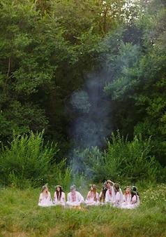 В середине лета. молодые люди в славянских одеждах сидят в лесу у костра.