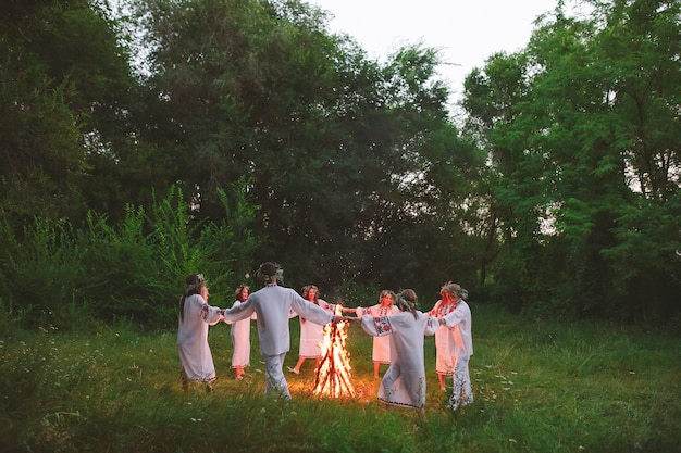 Midsummer. young people in slavic clothes circle dance around a bonfire in the forest.
