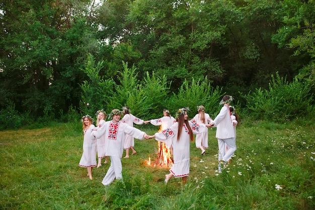 Midsummer, young people in slavic clothes revolve around a fire in the midsummer, .