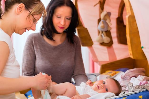 Midwife examining newborn baby