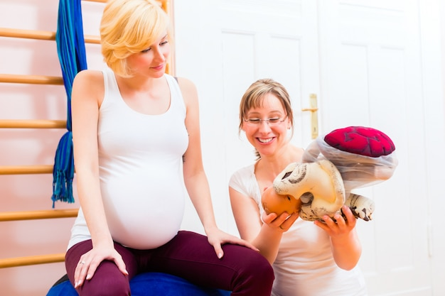 Midwife giving prenatal care for pregnant mother
