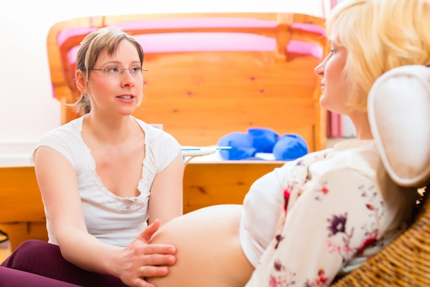 Midwife seeing mother for pregnancy examination