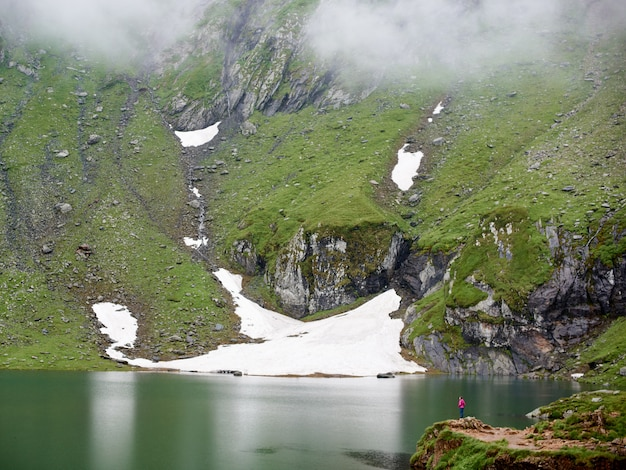 Mighty mountains are covered with fog and the lake at the foot