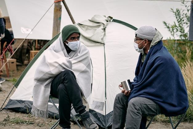 천막에 앉아 있는 이민자들
