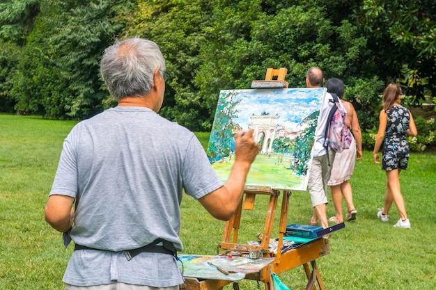 Milan, italy - 14.08.2018: artist draws arch of peace in sempione park.