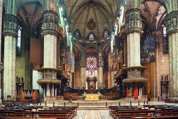 밀라노, 이탈리아 - 2014년 8월 17일: 밀라노 두오모 대성당 내부 인테리어. 제단과 벤치가 있는 갈기 본당