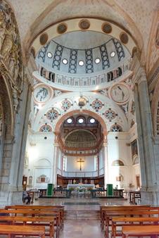 밀라노, 이탈리아 - 2014년 8월 17일: 밀라노 두오모 대성당의 내부. 제단과 벤치가 있는 본당