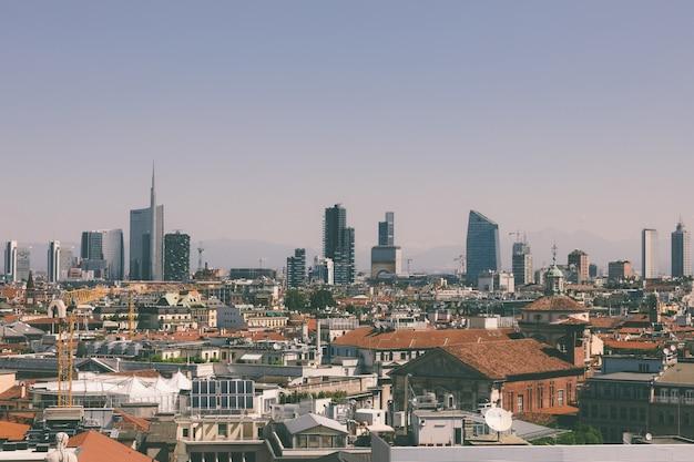 밀라노, 이탈리아 - 2018년 6월 27일: 밀라노 대성당(duomo di milano)에서 현대적인 건물이 있는 밀라노 시의 탁 트인 전망. 여름 화창한 날과 푸른 하늘
