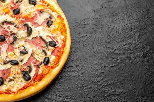Milanese pizza on a black background, tomato-based with mozzarella