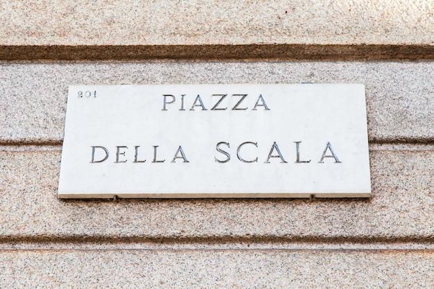 Милан, италия. уличный знак знаменитой площади ла скала перед театром ла скала