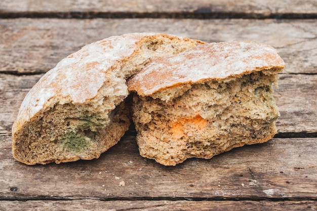 Mildew on a slice of bread, lying on a wooden surface. stale bread, covered with mildew