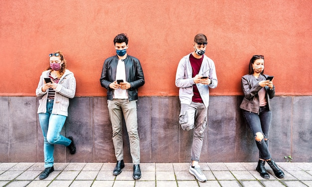 Milenial people using mobile smart phone covered by face mask
