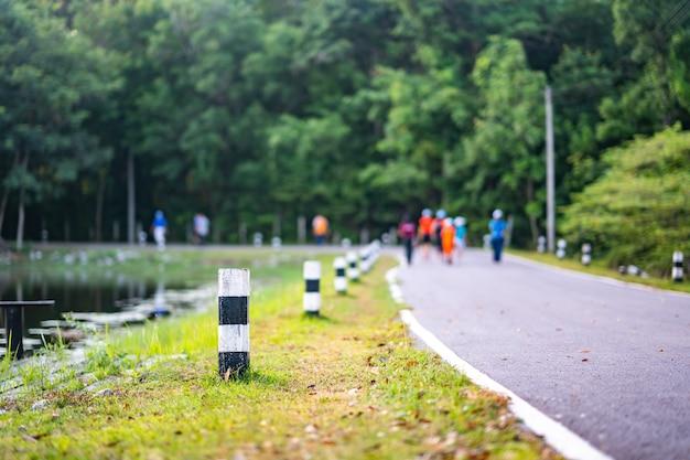 Milestone on road and blurred people walking on road