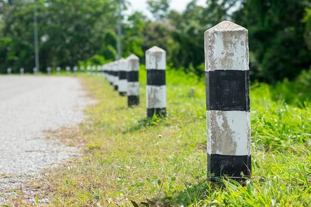 Milestones - black and white milestones with green grass roadside