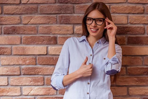 Женщина позирует miling, трогательно очки и показывает ок.
