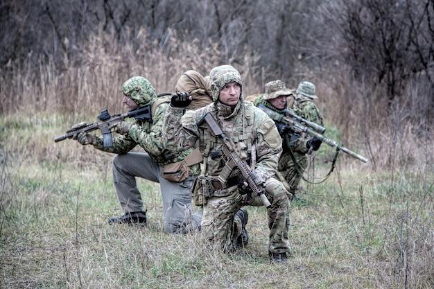 Тактическая группа солдат армии, группа коммандос осторожно передвигается в лесной зоне, стоит на коленях и оглядывается, прикрывая товарищей, контролируя секторы. командир показывает сигнал остановки или остановки