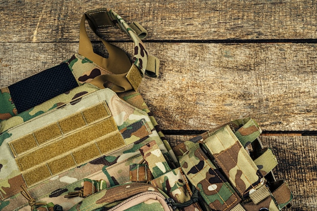Military body armor on wooden background close up