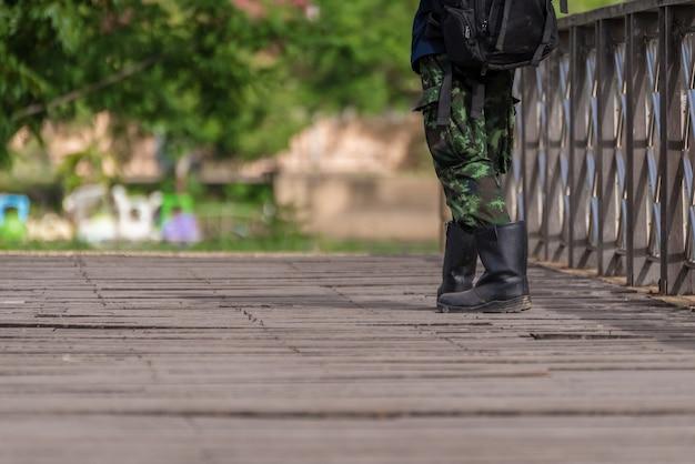 Military boots walking across a wooden bridge