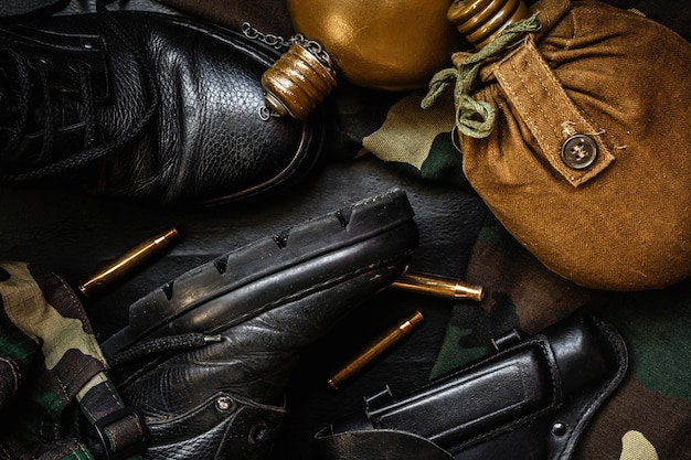 Military camouflage uniform and boots. a set of military items flask gun on a dark background