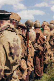 Военное строительство солдат во время реконструкции боевых действий в мае, узкая зона резкости, упор на винтовку. фото высокого качества