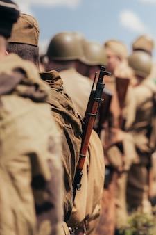 Военное строительство солдат во время реконструкции боевых действий в мае, узкая зона резкости, упор на винтовку