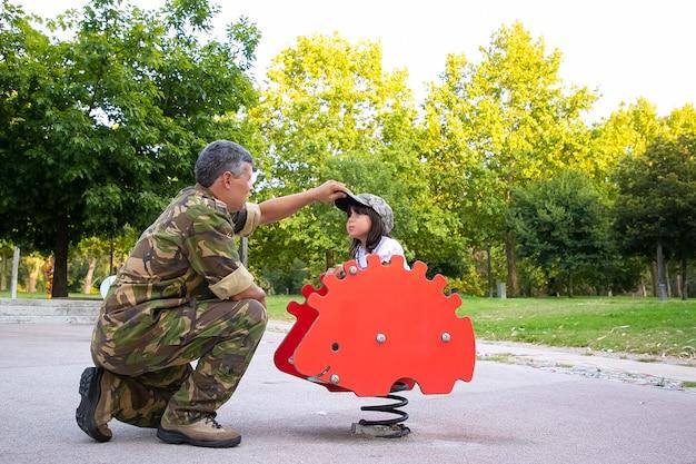 Papà militare che gioca con la figlia nel parco giochi, vestendo la ragazza con un berretto mimetico mentre cavalca un riccio a dondolo primaverile. genitorialità o concetto di infanzia