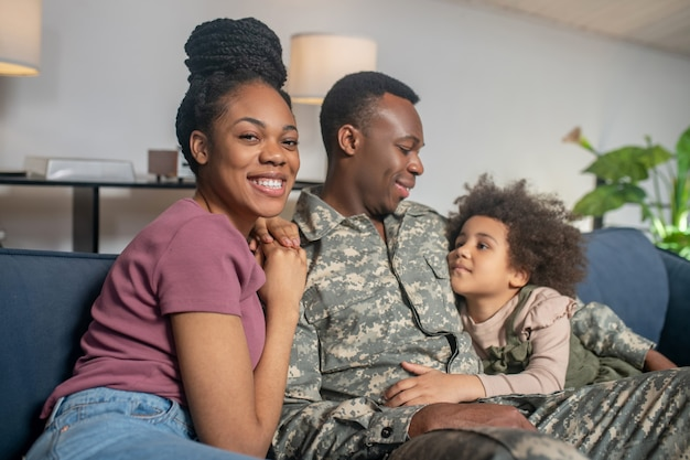 Military, dad. serviceman young darkskinned man in uniform sitting with happy wife and little daughter embracing on sofa on vacation at home