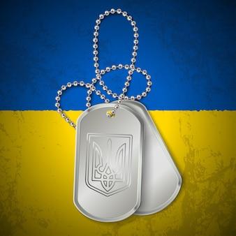 Военный жетон с национальными символами украины на грязном флаге. украинский конфликт.