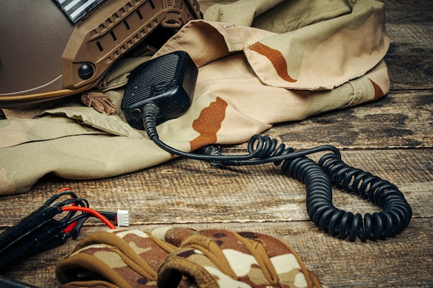 Military equipment, walkie-talkie with military uniform on wooden board