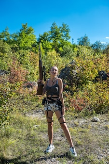 Military fashion woman with rifle, hot summer time, forest