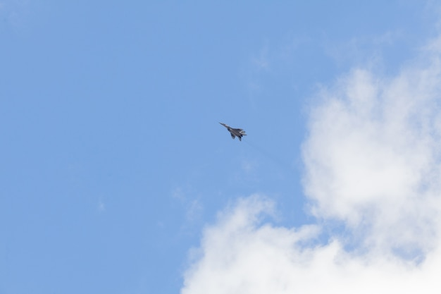 Military fighter in the blue sky with white clouds