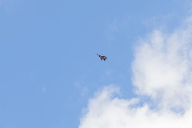 白い雲と青い空の軍の戦闘機