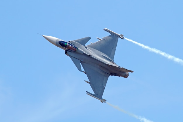 Military fighter jet on blue sky