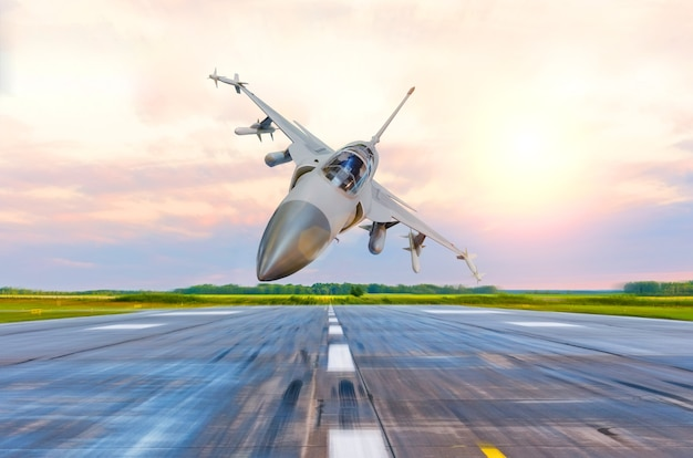 Military fighter jet flies at high speed over the taxiway at the airport.