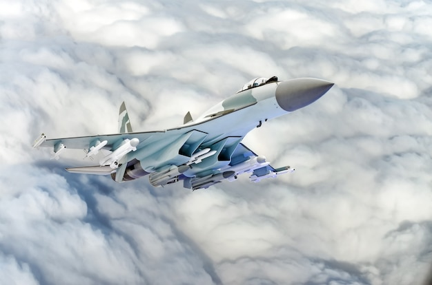 Military fighter jet plane above the clouds.
