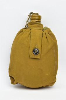 Military flask for liquid lined with khaki cloth with closed lid on a chain on white clipping background