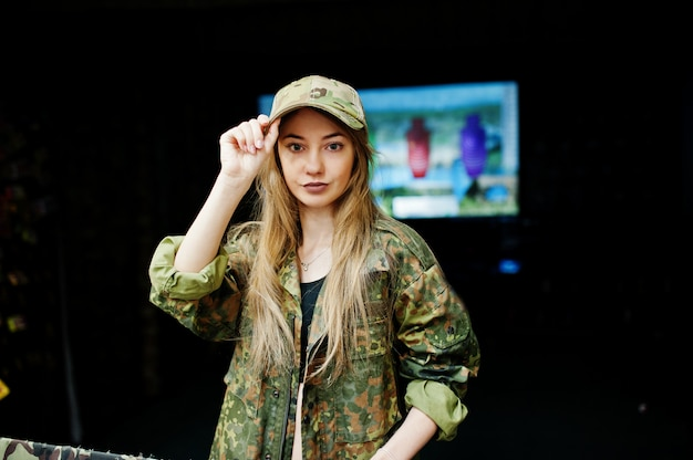 Military girl in camouflage uniform against army background on shooting range.